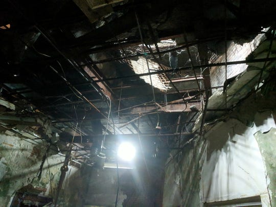 Sunlight pours in through gaping holes in the roof and ceiling at the old Howell bank building on the West Side. Water and time have destroyed the plaster leaving only steel beams in the ceiling.