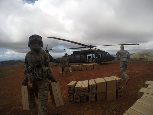 Spc. Darin Bookey, a Black Hawk crew chief with the 3rd Battalion, 501st Aviation Regiment, assists with delivering food and water to the residents of Jayuya, Puerto Rico.