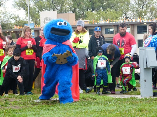 Children join the Cookie Monster to warm up by doing lunges right before they head off for Saturday's CASA run.