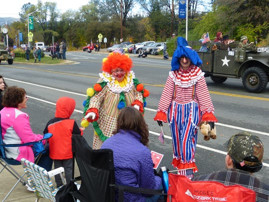 Two women dressed as clowns entertain the crowd that