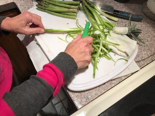 Barbara James learns how to peel asparagus
