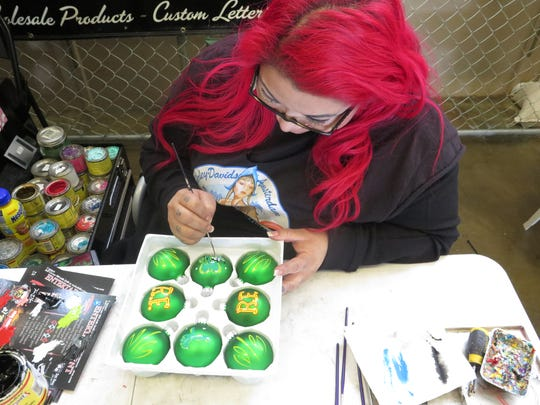 Katt Mercy paints Christmas tree ornaments for sale