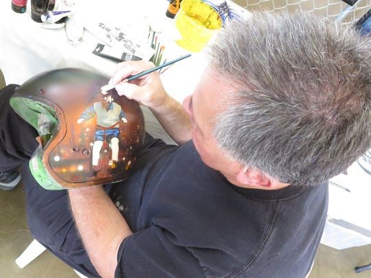 Jack Knight paints a motorcycle helmet at the 2016