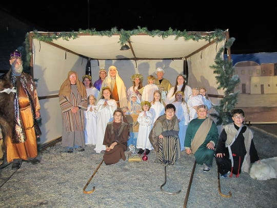 Cast of living nativity away in the manger of a past