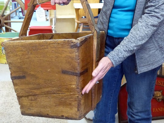 Kay enjoys the stories behind some of the antiques, including this wooden bucket with fitted joints.