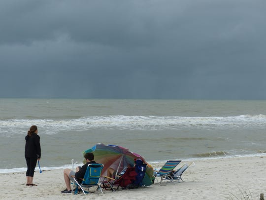 People relax on Vanderbilt Beach in North Naples on Saturday, Dec. 9, 2017, despite cloudy, cooler weather. A cold front was forecast to bring near-record lows to Southwest Florida. Temperatures could dip into the low 40s by Sunday morning, Dec. 10.