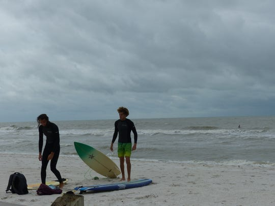 Surfers take a break from riding choppy surf off Vanderbilt Beach in North Naples on Saturday Dec. 9, 2017. A cold front is forecast to bring near-record lows to Southwest Florida. Temperatures could dip into the low 40s by Sunday morning, Dec. 10.