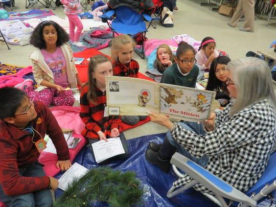 Students enjoy a book read by fourth-grade teacher Ellen Colandrea of North Plainfield.