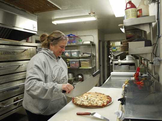 Laura Reis, co-owner of Anchor In Bar & Grill at Marinatown in North Fort Myers, gets ready to cut the pizza into Midwestern-style square slices.