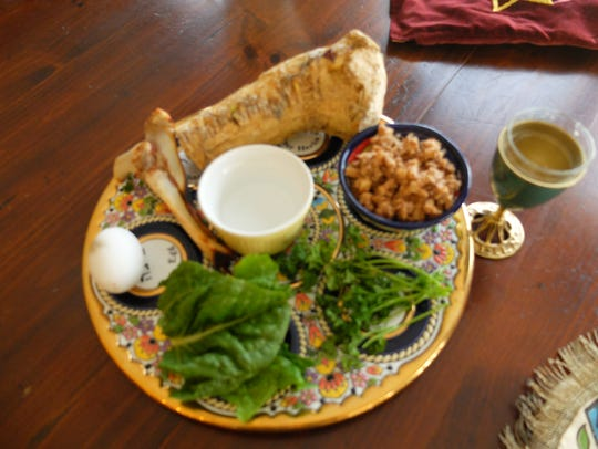 A Passover Seder plate. Beside it stands the cup for