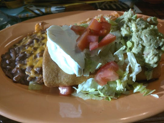 El Tapatio Mexican Grill's super chimichanga was a tortilla  jam-packed with marinated pulled chicken breast and served with rice, refried beans with melted cheese on top, lettuce, tomato, guacamole and sour cream.