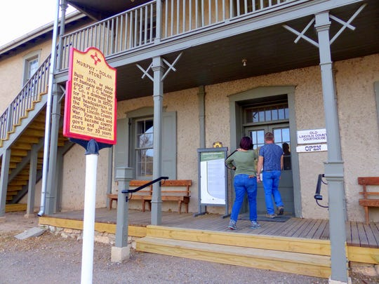 Visitors are about to enter the old Lincoln courthouse, where Billy the Kid was jailed and killed two lawmen while escaping.