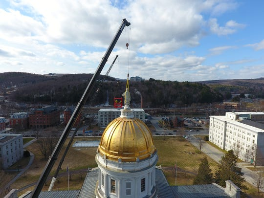 A statue of Ceres, the Roman goddess of agriculture, is removed from the Vermont State House dome for restoration on Monday, April 2, 2018.