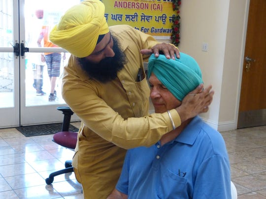 Gurdip Singh of Cottonwood smooths out the turban he tied on Lee Shoop of Red Bluff at the Sikh Centre in Anderson on Saturday.