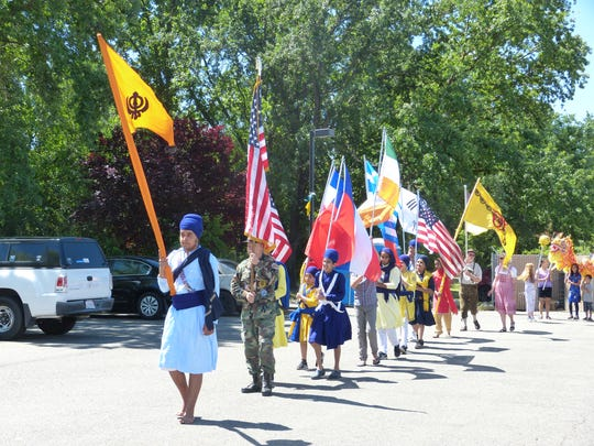 People walk around the Sikh Centre of Anderson with various flags Saturday as part of the Vaisakhi Festival. The leading flag, known as Nishan Sahib, is a flag that represents Sikhs.