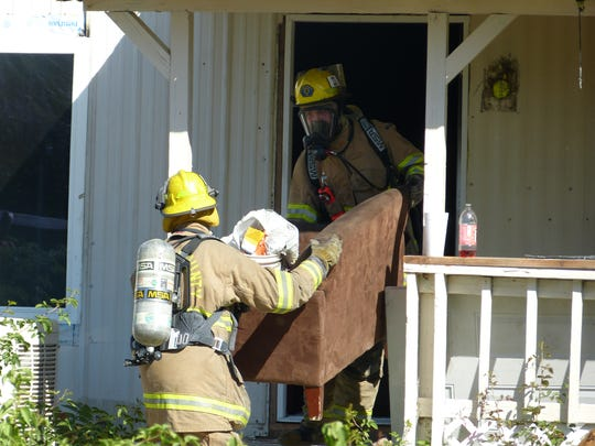 Firefighters remove a sofa from a still-smoldering mobile home Tuesday in Bella Vista.