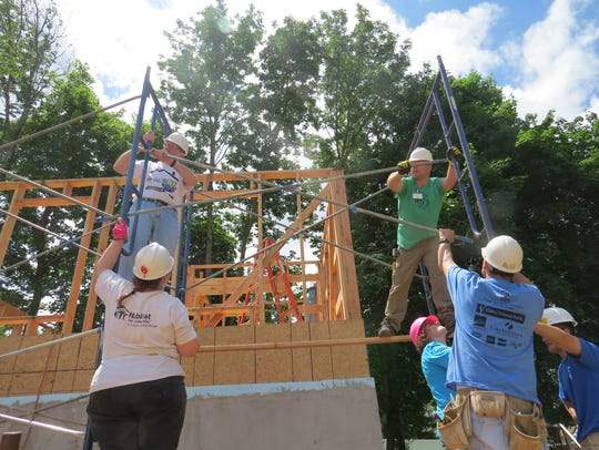 Volunteers work on one of three houses being constructed