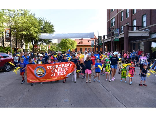 Children in costumes and carrying a banner lead the Storybook Parade during last year's Children's Art & Literacy Festival.