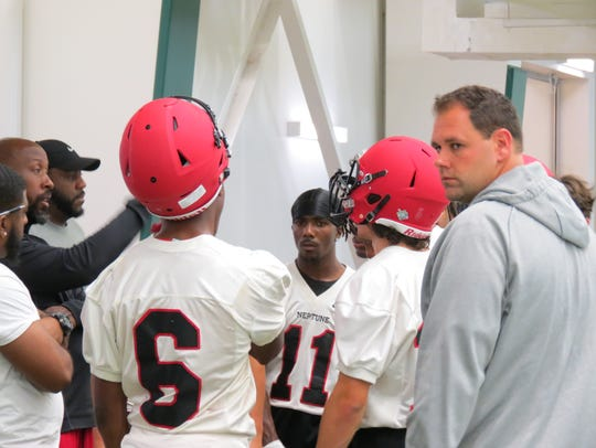 Neptune coach Tarig Holman (left) instructs his players