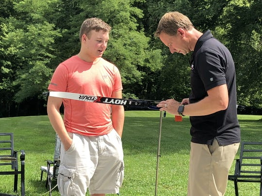 Dalton Hinkle, left, talks with Hoyt Archery engineer Doug Denton while he helps Hinkle set up his Olympic recurve bow that Hinkle received as a prize for winning the NASP national tournament in May.