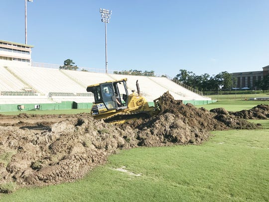 Construction trucks dig through the ground to prep for the turf installation.
