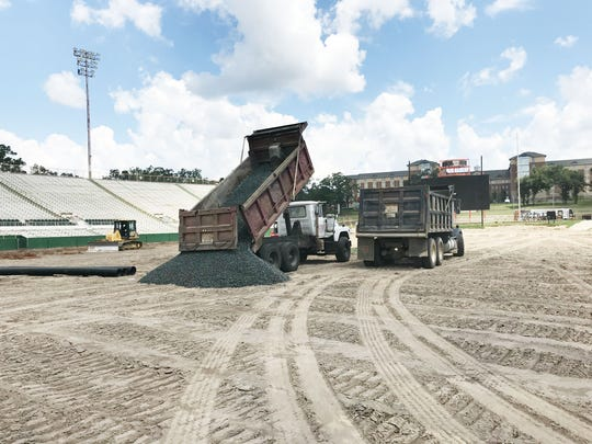 Dump trucks unload pounds of material during working sessions at Bragg Memorial Stadium.