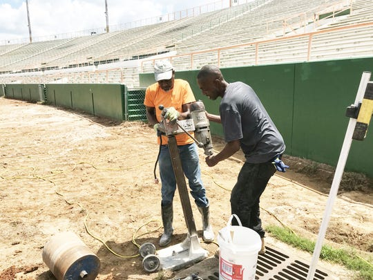 Terry Smith, left, and Samuel Moseley, Jr. of Great Southern Demolition team up to install a working cone drill.