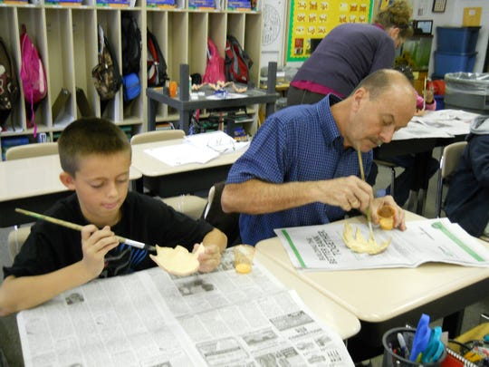 Jim Griffin, right, paints a leaf bowl alongside a former student at Black Mountain Elementary School, where Griffin taught for 15 years before retiring at the end of last year.