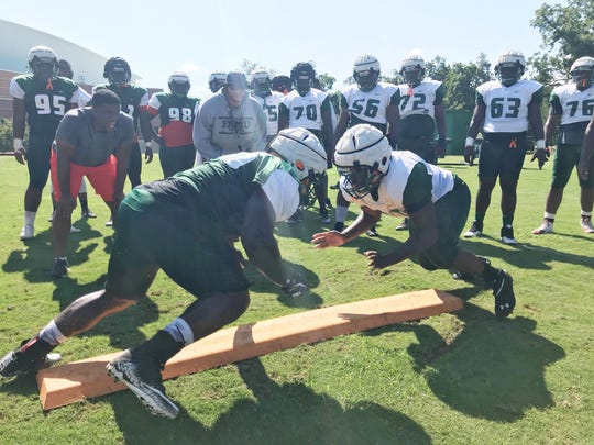 FAMU players engage in one-on-one blocking drills.
