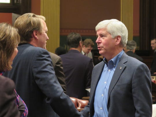 Michigan Gov. Rick Snyder visits the House chamber after it passed energy legislation, Thursday, Dec. 15, 2016, in Lansing, Mich.