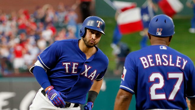 Texas Rangers' Joey Gallo rounds third past base coach Tony Beasley (27) on his way home following Gallo's two-run home run against the Kansas City Royals during the second inning of a baseball game in Arlington, Texas, Friday, April 21, 2017. (AP Photo/Tony Gutierrez)