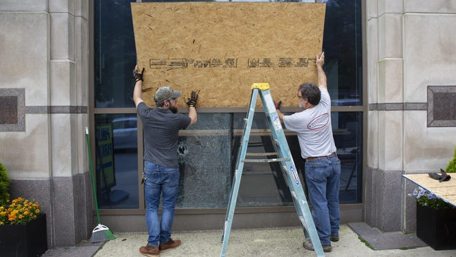 A crew from Neverman Construction boards up the broken windows of the Fifth Third building the morning after protests in the streets of Columbus on Friday. Businesses damaged in the protests could be eligible for property tax breaks.