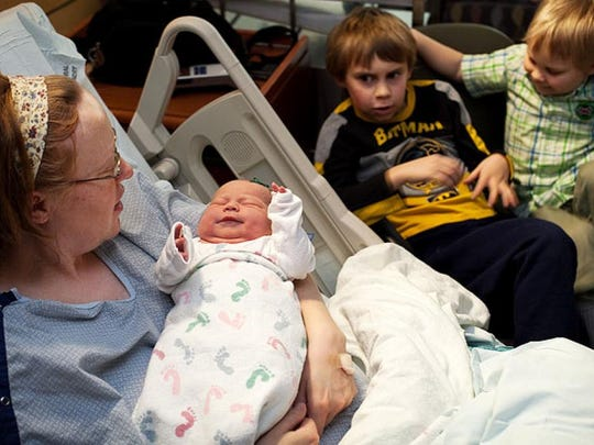 Louise Estes holds her new-born daughter Jade in 2012 as her sons, Xavier, 8, and Remington, 4, look on. All three children were born on Feb. 29.