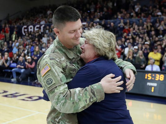 U.S. Army solider and Saint Mary's graduate Michael Sparks, left, hugs his mother Marianne after surprising her during an NCAA college basketball game between Saint Mary's and Santa Clara in Moraga, Calif., Saturday, Feb. 24, 2018. (AP Photo/Jeff Chiu)
