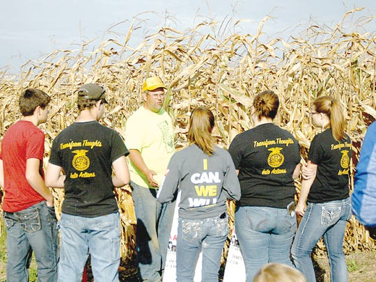 Clay Geyer, Indiana Corn Husking Association President, explains the rules of the corn husking contest to young people who were participating.