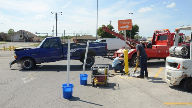 Workers use a jackhammer to dig the notorious Walmart pole out of the store's parking lot Friday as a Ford F-150 pickup truck that hit the pole more than a week ago is towed away. -- JONATHAN RILEY/THE MORNING SUN