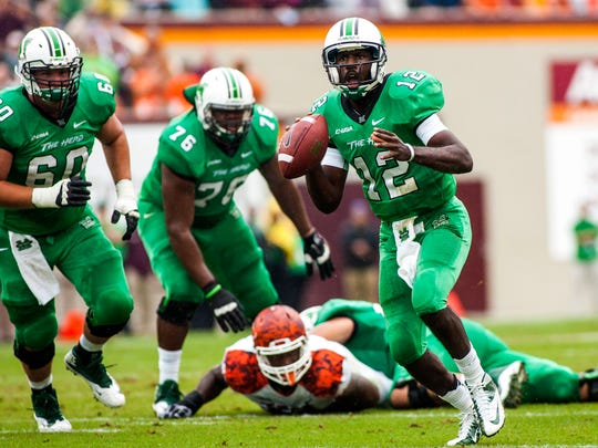Marshall quarterback Rakeem Cato (12) passes for a touchdown during the first quarter against Virginia Tech at Lane Stadium.