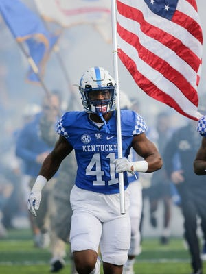 Kentucky linebacker Josh Allen carries the American flag as the team took the field before the first half of an NCAA college football game against Mississippi Saturday, Nov. 4, 2017, in Lexington, Ky.