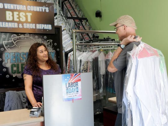 Veronica Salas, a clerk, helps Daniel Gallagher, with his dry cleaning at Persnickity Dry Cleaners in Ventura.