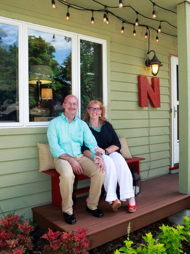 Erin and Mike Napier on the front porch of their home.