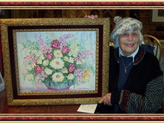Isabelle Berner is shown with one of her paintings.