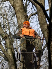 Dan Snyder, of Port Huron, sits in a tree stand wearing hunter orange.