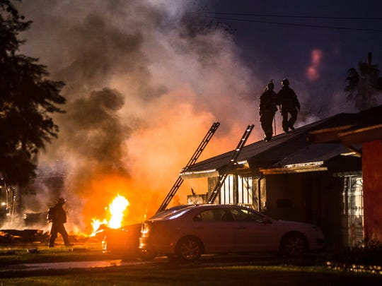 Smoke rises from a fire after a plane crashed in Riverside, Calif., Monday, Feb. 27, 2017. The deadly crash injured several when a small plane collided with two homes Monday shortly after taking off from a nearby airport, officials said.
