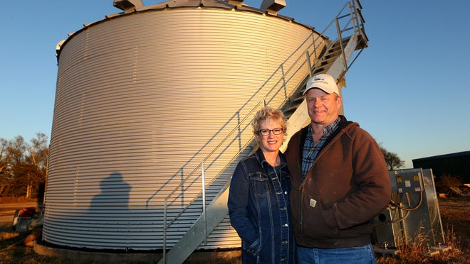 Kelly and Dale Love stand in front of one of their grain bins at their farm southwest of Partridge. The Love family has been named the Farm Focus Family of the Year by the Hutchinson/Reno County Chamber of Commerce.