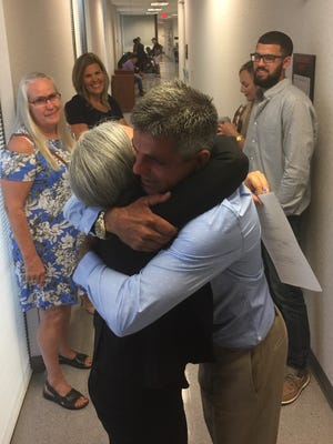Rudy Blanco hugs his lawyer, Gisela Rodriguez, after leaving an immigration courtroom in Orlando. His wife Shelly and son Noah beam with joy in the background.