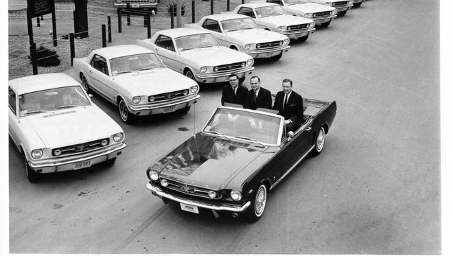 Mustang on its first anniversary, toting Ford executives Don Frey, left, the product chief who conceived the car; Lee Iacocca, who marketed the car brilliantly to buyers; Henry Ford II, CEO who finally gave up and approved the Mustang  after Frey and Iacocca pitched him on the car five times.