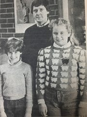 Sturgis Elementary students, Jama Wells, left, and Sarah Whitehead, right, pose with principal John Belt. Jama placed first and Sarah placed second in the Soil Conservation poster contest in December 1985.