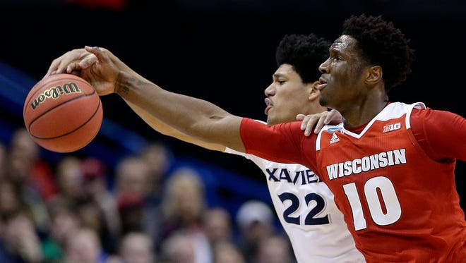 Wisconsin's Nigel Hayes (10) and Xavier's Kaiser Gates (22) chase the ball during the first half of a second-round men's college basketball game in the NCAA Tournament on Sunday in St. Louis.