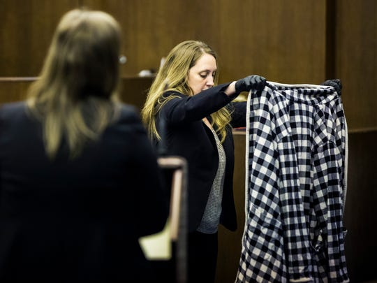 Kimberly Costa, a crime scene investigator with the Collier County Sheriff's Office, presents Lisa Troemner's robe — a piece of evidence from the night of the homicide — to the jury during Troemner's trial at the Collier County Courthouse in East Naples on Monday, Jan. 22, 2018.