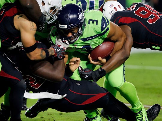 Kareem Martin of the Cardinals hits Seahawks quarterback Russell Wilson during Thursday's game in Glendale, Arizona.